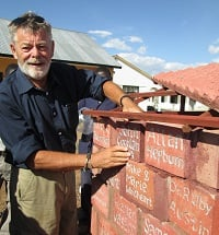 John Coghlan building red bricks in Africa