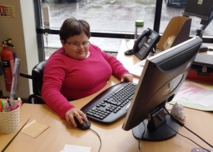 Cathy Curran at her desk on the computer