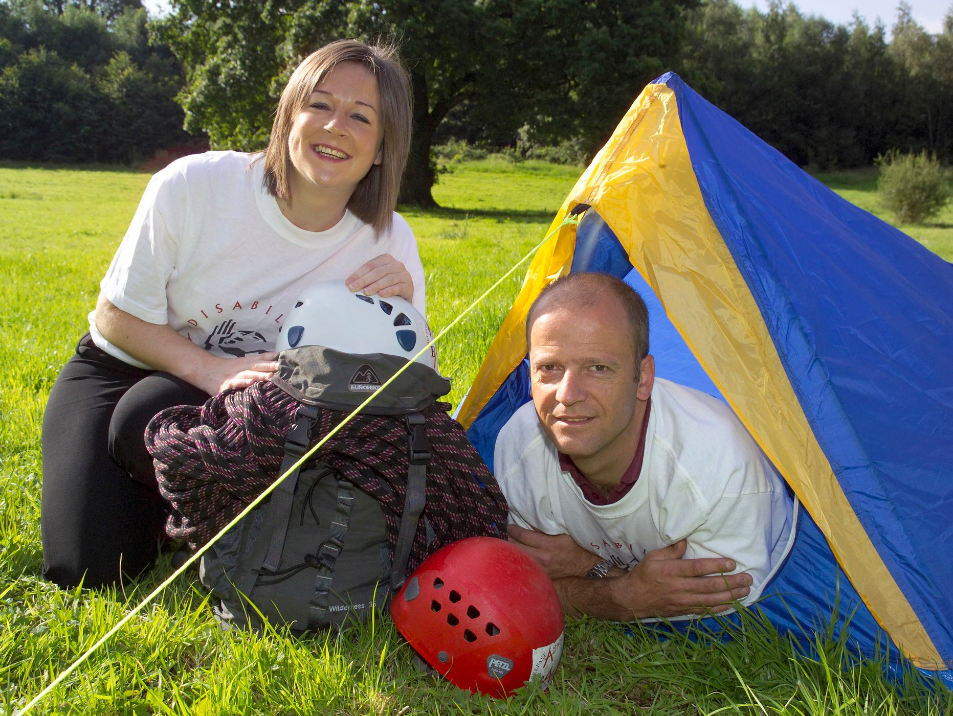 Image of Darren Campbell in a tent and Clare Sheeran from Disability Action in a Disability Action t-shirt