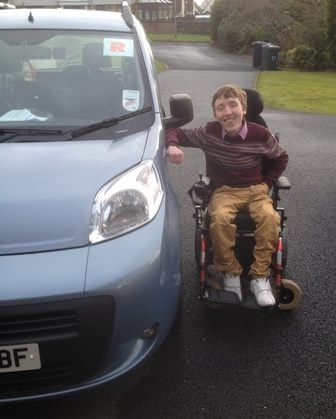 wheelchair user Conor Smyth beside his car after he passed his driving test